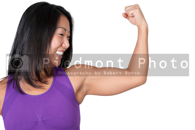A beautiful young Asian woman flexing her muscles during a workout