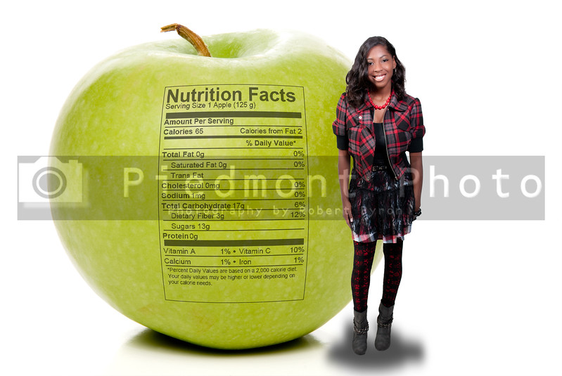 A beautiful teenage African American woman standing beside a green Granny Smith apple