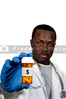 prescription medication pill bottle being held by a blurred Black man African American doctor