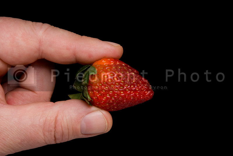 A person holding a Strawberry in their fingers