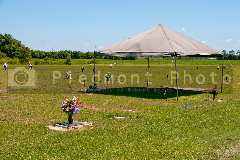 A tent or cover creating shade at a cemetery grave site