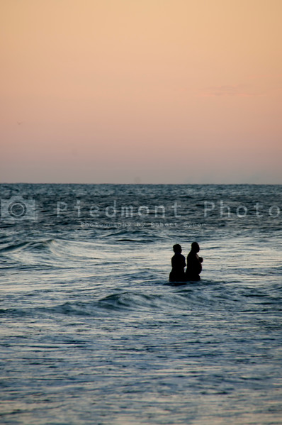 A couple of late evening silhouetted swimmers at the beach