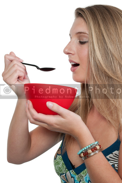 A beautiful woman eating food from a bowl