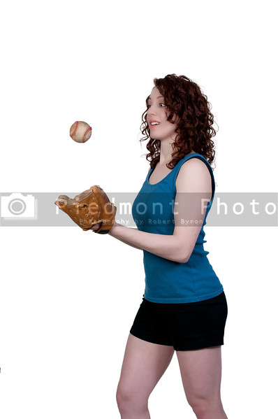 A beautiful woman throwing a baseball into the air