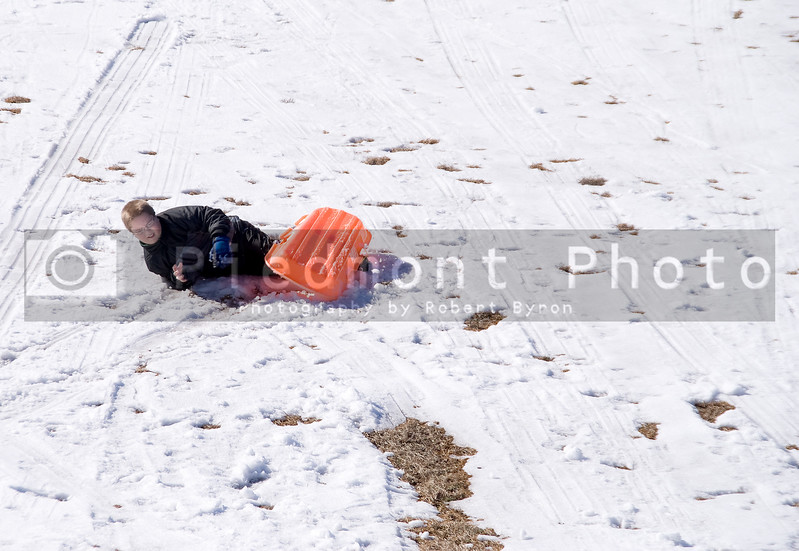 A young boy wrecking his sled at the bottom of a hill.