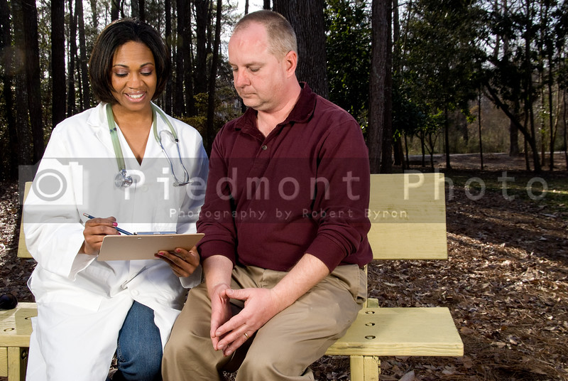 A doctor gong over a medical chart with a patient.