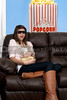 Beautiful young woman watching a 3d dvd movie on tv at home