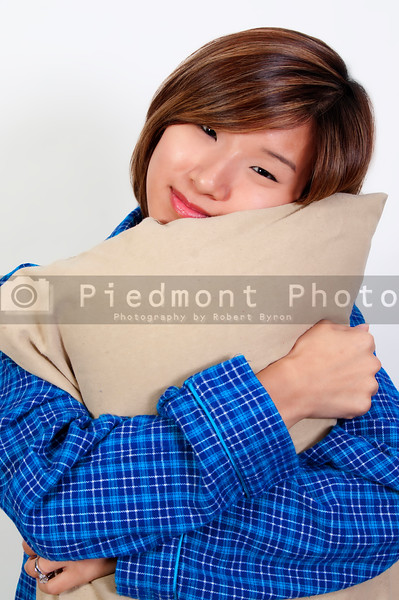 A beautiful young Asian woman wearing pajamas hugging her pillow
