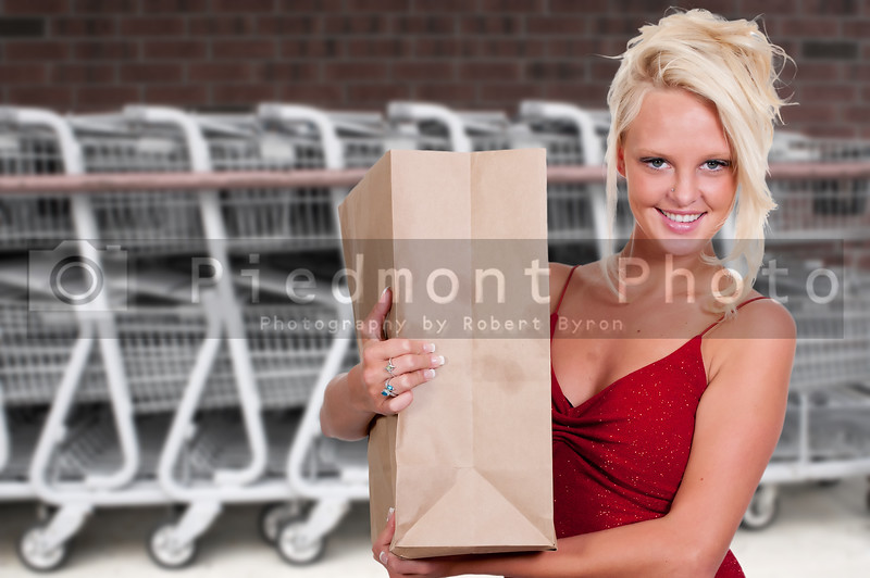 A beautiful young woman on a shopping spree with a brown paper bag