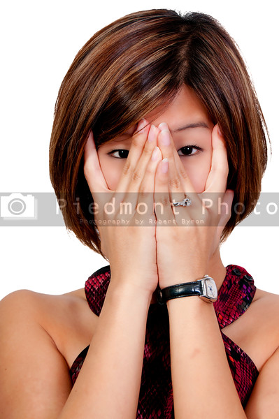 A beautiful young scared or surprized Asian woman looking through her hands