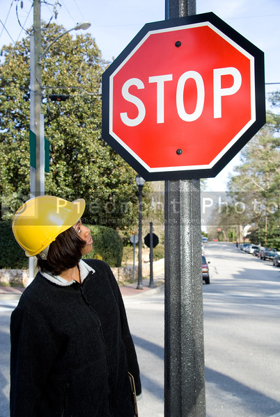 A female construction worker inspecting a stop sign.