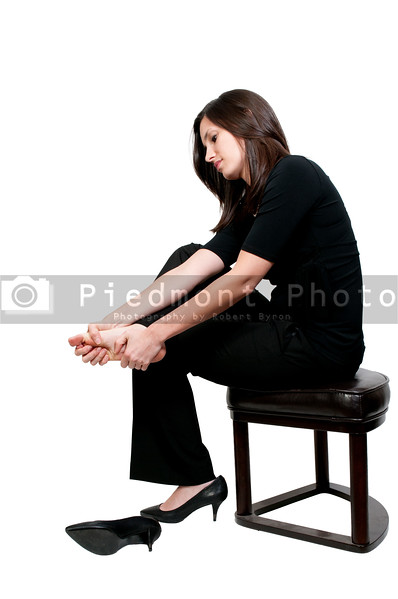 A beautiful young business woman rubbing her sore tired feet