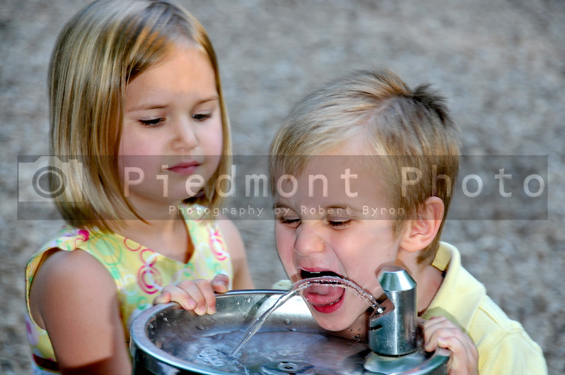 A little boy drinking water at a playground