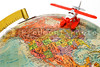 A toy palne flying over a globe.