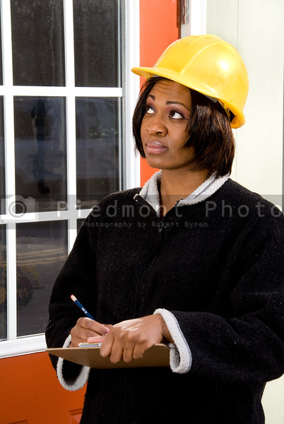A Female Construction Inspector checking on the integrity of a building