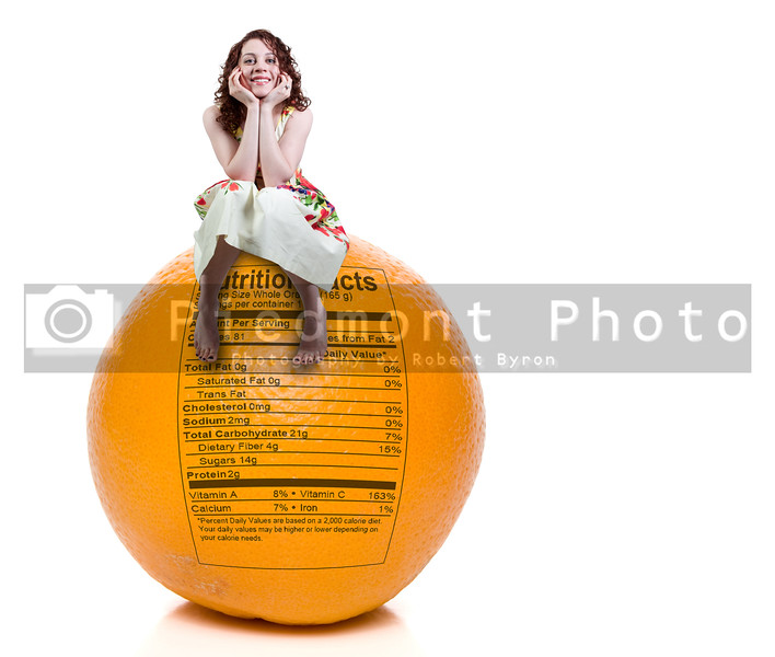 A woman sitting on a delicious orange with nutrition facts