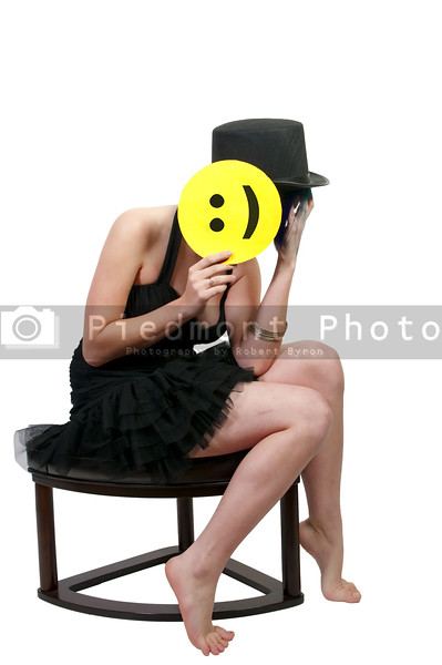 A beautiful depressed young woman hiding behind a smiley face