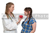 A female cardiologist holding a red heart while talking to a woman patient