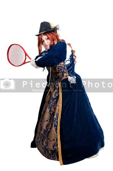 A woman dressed as a renaissance aristocrat in authentic dress playing tennis