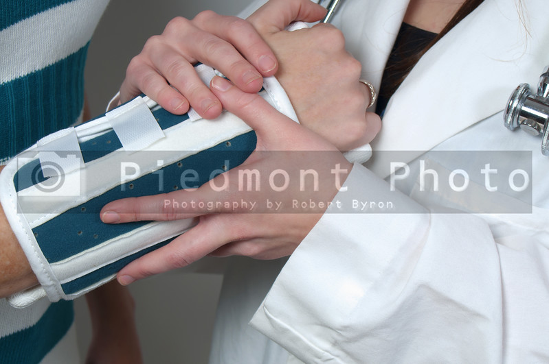 A beautiful young female doctor applying a arm brace to a patient