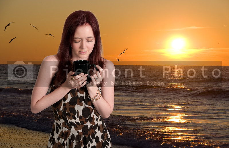 A beautiful young woman drinking coffee at the beach in the morning