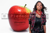 A beautiful teenage African American woman standing beside a red delicious apple