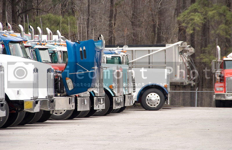 A group of Tractor Trailor Trucks in a parking lot
