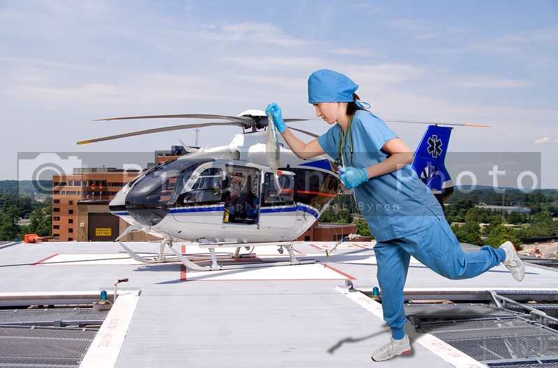 A beautiful young female doctor holding an IV bag in front of a medical ambulance helicopter
