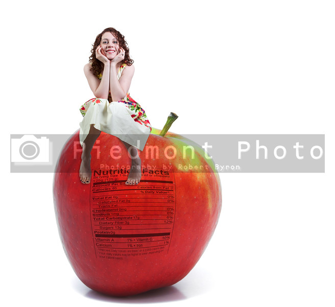 A beautiful young woman sitting on a whole red delicious apple with a nutrition label