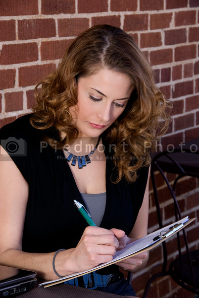 A beautiful young woman filing out a form.