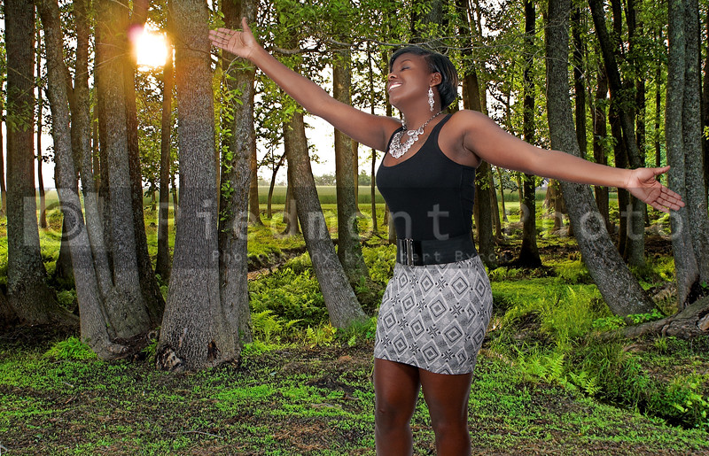 A beautiful young African American black woman standing in a green spring forest