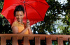 A beautiful young black woman holding an umbrella
