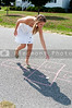 A beautiful woman engaged in the childhood game of hopscotch