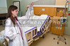 A beautiful young female doctor holding an IV bag in a hospital room
