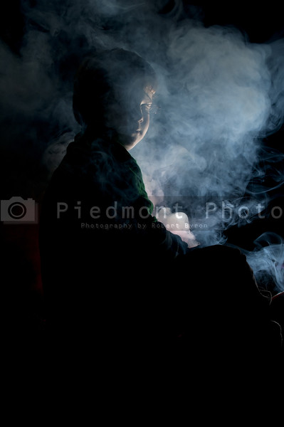 A young boy enveloped in fog or smoke