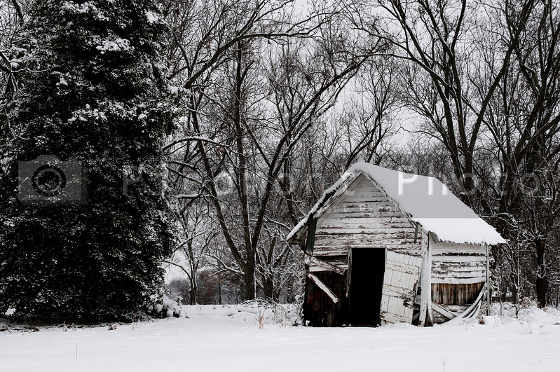 An old abandoned outbuilding covered in a winter snow storm