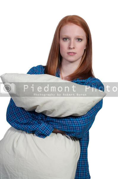 A beautiful young woman wearing pajamas hugging her pillow