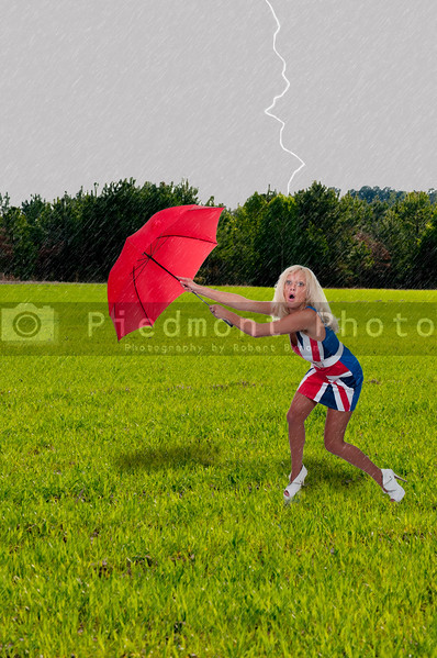 A beautiful woman holding a colorful umbrella in the wind and rain