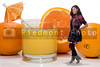 A beautiful young teenage African American woman with a glass of orange juice with an umbrella and slice.