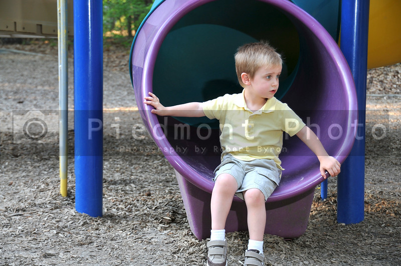 A young boy on a slide at a park