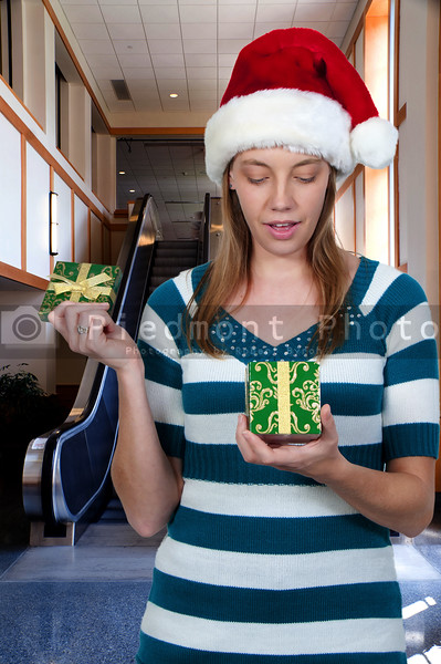 A beautiful woman opening a Christmas present gift