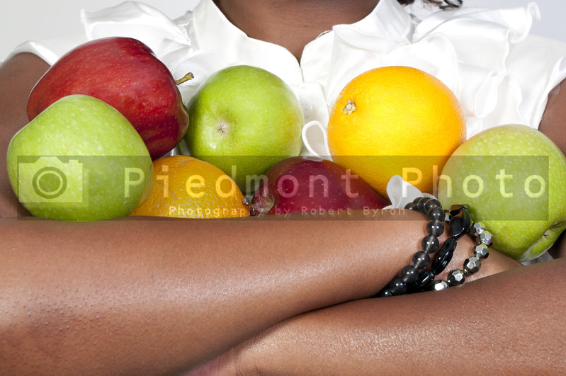 A black woman holding an assortment of fruit
