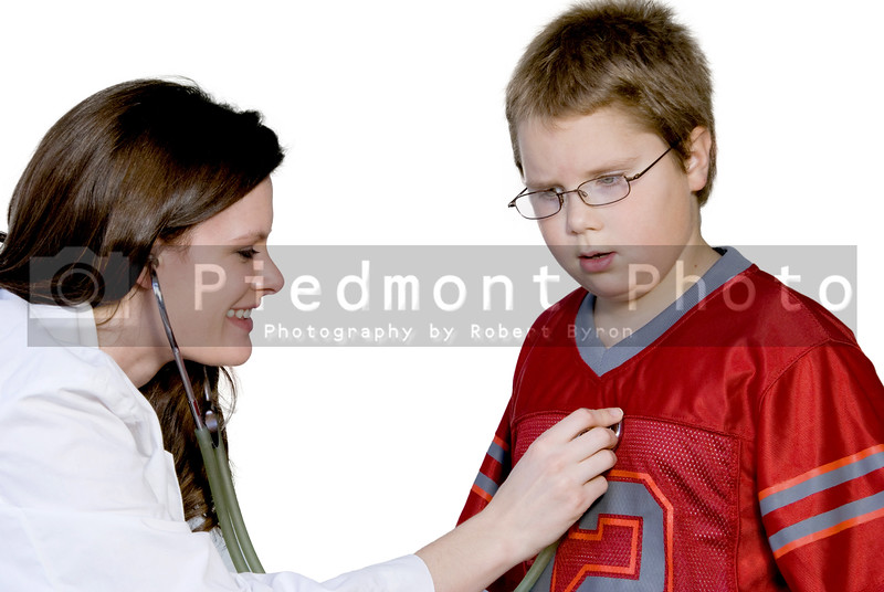 A Female Pediatrician examining a young boy