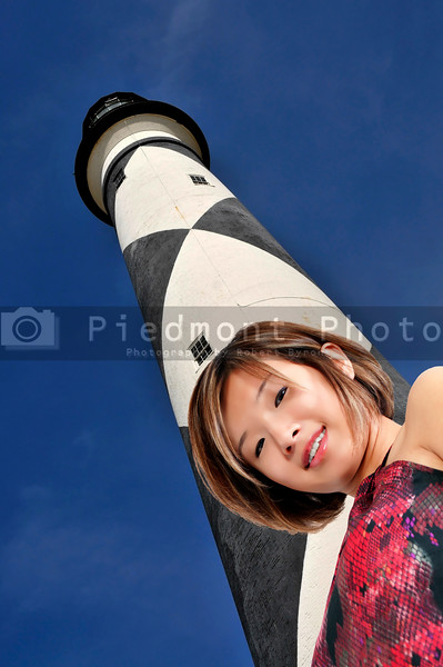 A beautiful young Asian woman tourist on vacation at a historical lighthouse