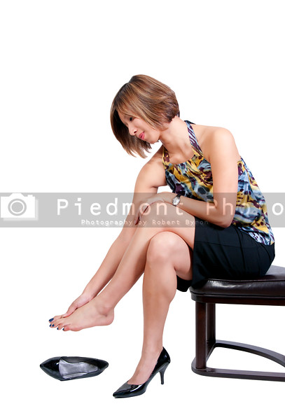 A beautiful young Asian business woman rubbing her sore tired feet