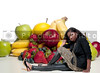 A beautiful young teenage woman sitting beside a wide assortment of delicious and fresh fruits