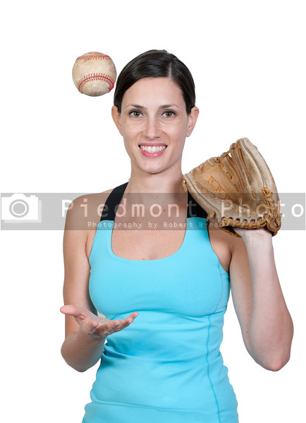 A beautiful woman catchinging a baseball at a ball field