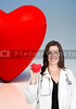 A female cardiologist woman doctor holding a red heart