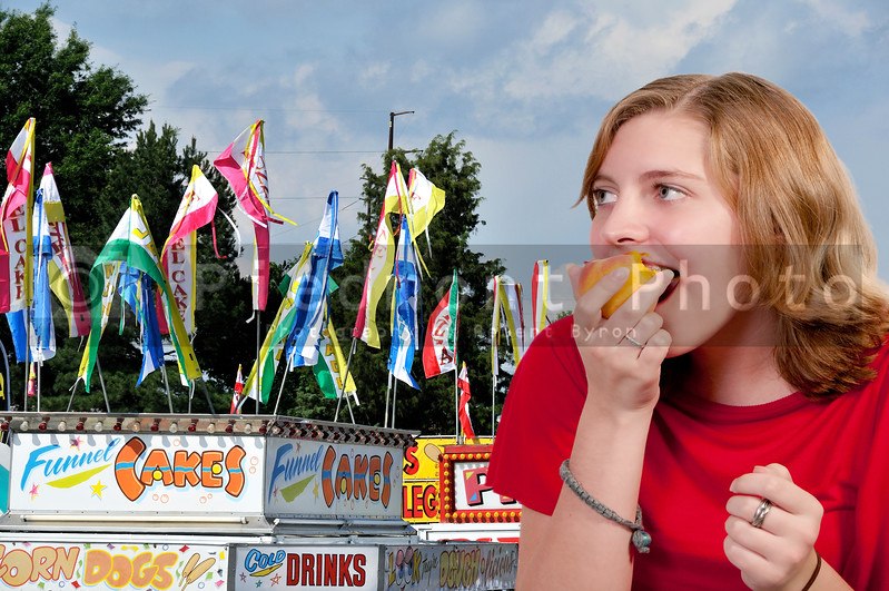 A girl on a carnival midway eating a peach