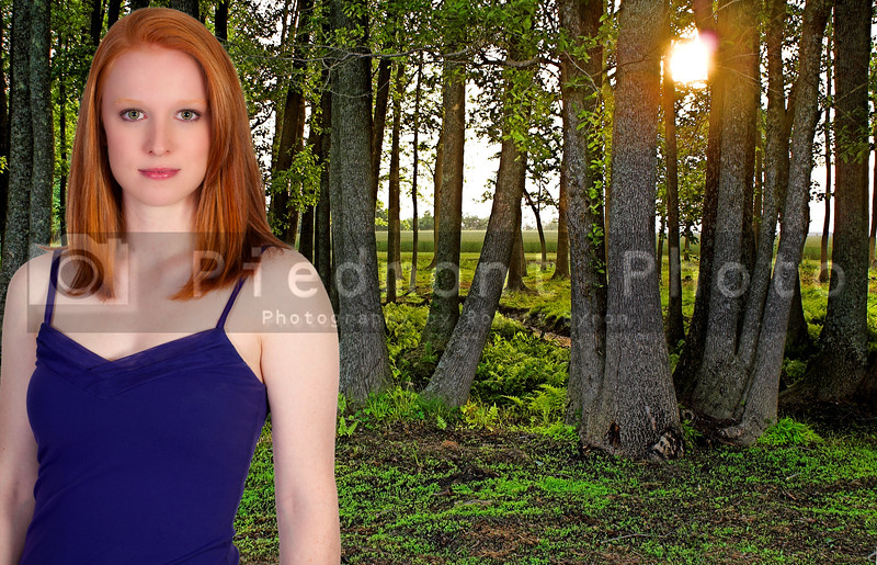 A beautiful young woman standing in a green forest in the early spring of the year.